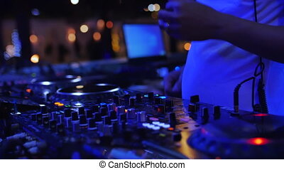 DJ sound control console for mixing dance music and laptop in disco club. Hands touching buttons sliders, playing electronic music on mixing deck, color illumination in nightclub dance party. Close up