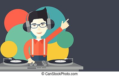 DJ with console. - An asian DJ wearing headphones and...