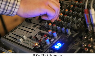 DJ works on the mixer console. Hand adjusting audio mixer -...