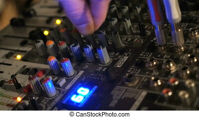 DJ works on the mixer console. Hand adjusting audio mixer