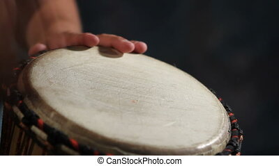 Djembe Drumbeat - Closeup of man\\\'s hands drumming out a...