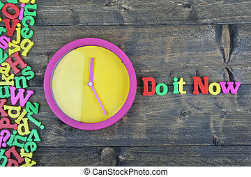 Do it now on wooden table - Do it now word on wooden table