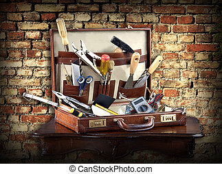An assortment of services and maintenance tools in a leather case against a grunge brick background