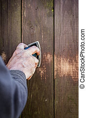 Do it yourself, closeup hand with a electric sander on wooden boards or fence