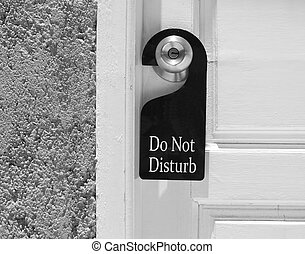 Do not disturb sign hang on door knob and stone wall.