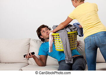 Do the laundry - A woman giving her husband dirty clothes to...