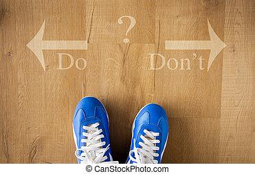 DO versus DON`T written with arrows on wooden floor