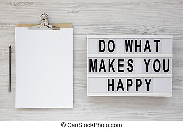 'Do what makes you happy' words on a lightbox, clipboard with blank sheet of paper on a white wooden background, top view. Overhead, from above, flat lay.