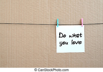 Do what you love. Note is written on a white sticker that hangs with a clothespin on a rope on a background of brown cardboard