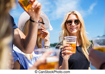 A photo of young, beautiful woman drinking beer with her friends and smiling.