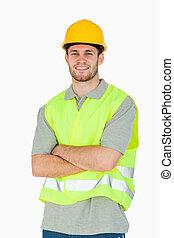 doblado, sonriente, construcción, brazos, trabajador, joven