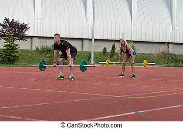 dobrado, pessoas, sobre, jovem, barbell, exercício, fila