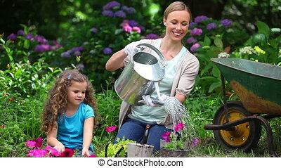 dochter, haar, schouwend, watering, terwijl, moeder, bloemen