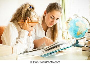 dochter, schoolboek, terwijl, moeder, lezende , huiswerk