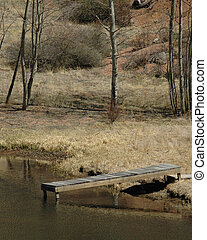 Dock - A wooden dock leading into a lake hidden amongst the ...