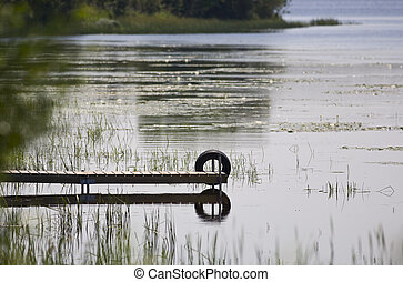 Dock and Tire Reflecting - A dock and tire reflecting in the...