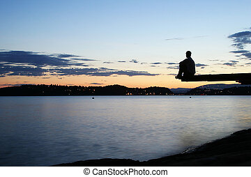 Dock at Dusk - A young person sitting on a dock at dusk, at...