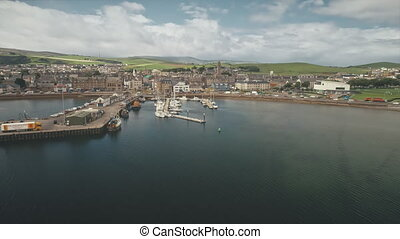 Dock at pier town cityscape aerial. Seagull flight over ocean bay. Yachts, vessels at wharf. Old buildings architecture landmark at urban streets of Campbeltown city, Scotland. Cinematic seascape