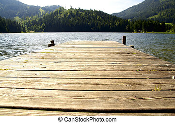 Dock in a lake - Small dock leading in a lake in the Alps