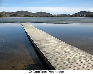 A long gray dock juts diagonally into a pristine, half-frozen mountain lake.