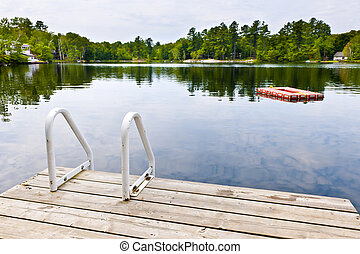 Dock on calm lake in cottage country - Dock and ladder on ...