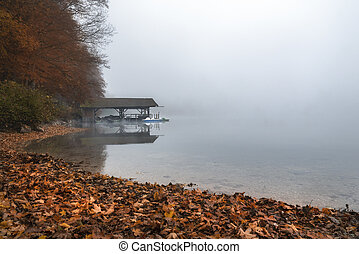 Dock on lake in autumn fog