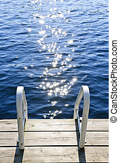 Dock on summer lake with sparkling water - Dock and ladder...