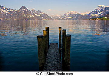 Dock - Empty dock in calm lake with mountains in the...