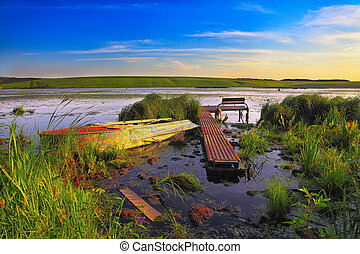 dock with boat on the lake at sunset