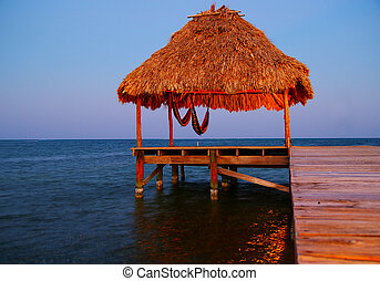 dock with tropical thatched roof palapa at dusk