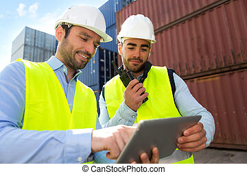 Dock worker and supervisor checking containers data on tablet