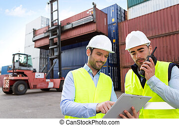 Dock worker and supervisor checking containers data