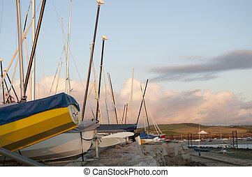 Docked Hulls - Low angle shot of small boats hulls against...
