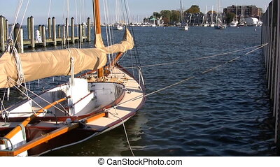 Docked Sailboat - Small wood sailboat is docked at a pier in...