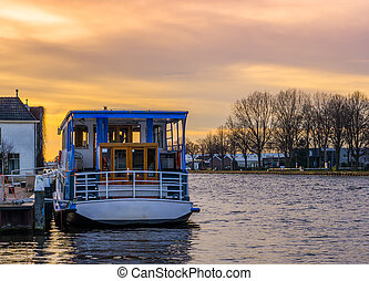 docked touring boat in the harbor at sunset, beautiful colorful sky with city scenery