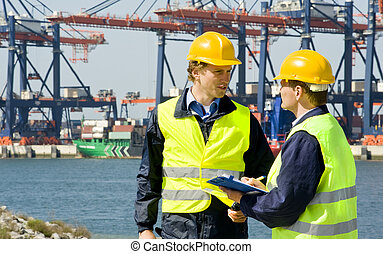 Two dockers at work in a big container harbor