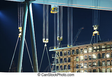 Detail of cranes and hooks in a shipyard by night