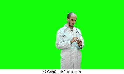 docteur masculin, chroma, étiquette, écran, vert, key., bouteille, médecine, lecture, attentivement, pilules