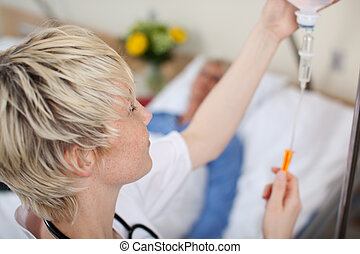 Doctor Adjusting Infusion Bottle With Patient Lying On Bed -...