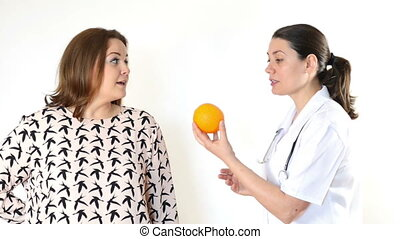 Doctor advising a fat woman to eat healthy. Fat woman eating...