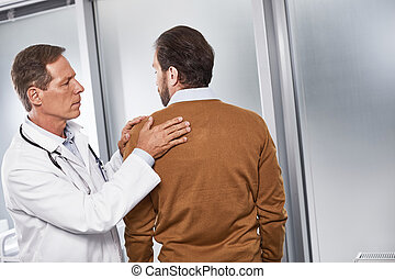 Doctor analyzing reasons of pain in shoulder joint