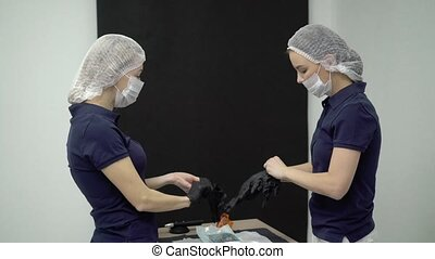 Doctor and assistant put on mask - Doctorand assistant put...