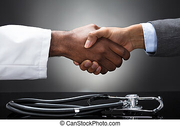 Doctor And Business Man Shaking Hands With Stethoscope On Desk