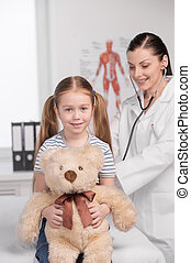 Doctor and child. Cheerful young doctor in lab coat...