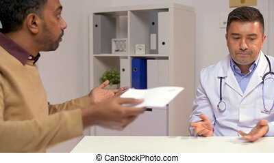 doctor and displeased male patient at clinic - medicine,...