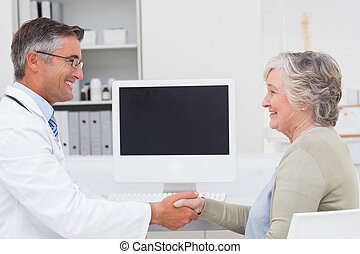 Doctor and female patient shaking hands