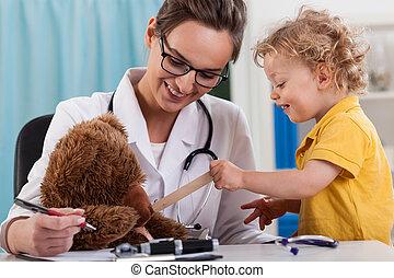 Doctor and little boy examining a teddy bear
