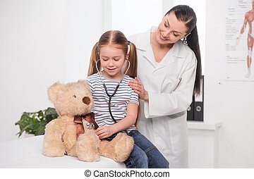 Doctor and little girl. Cheerful young doctor in lab coat examining little girl with stethoscope