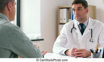 doctor and man with health problem at hospital - medicine,...
