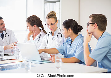 Doctor and nurse discussing over laptop